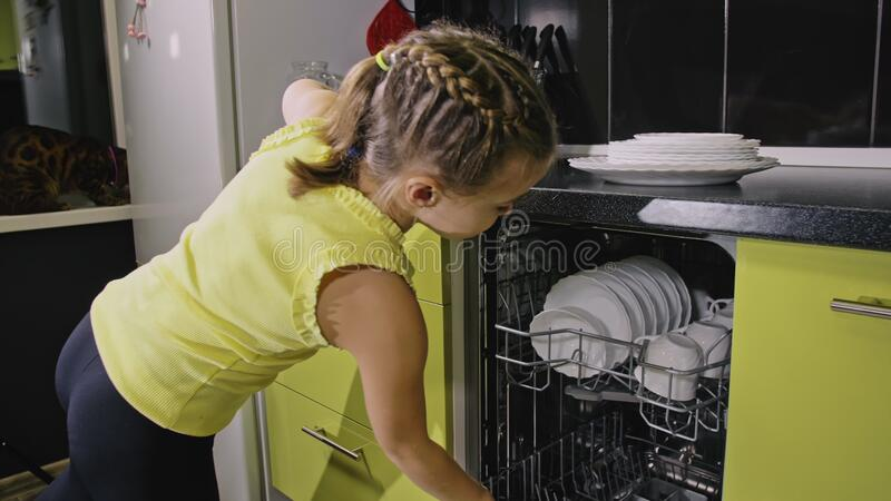 Smart girl learning to use dishwasher. Stylish modern Built In Kitchen Appliances in green black. Child is putting clean. Smart girl learning to use dishwasher stock images