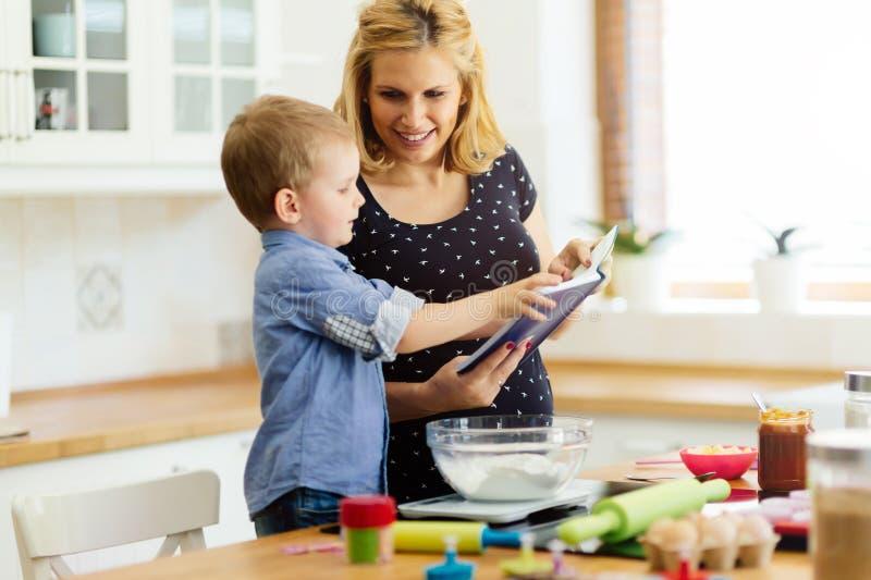 Smart gullig barnportionmoder i kök royaltyfria bilder