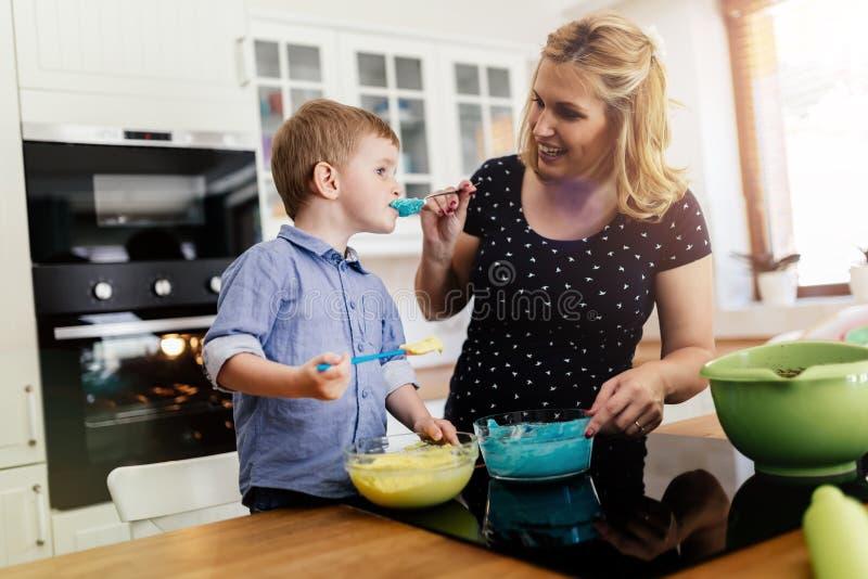 Smart gullig barnportionmoder i kök royaltyfri fotografi