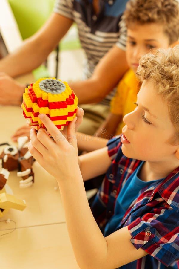 Smart gullig pojke som ser leksakballongen royaltyfria bilder
