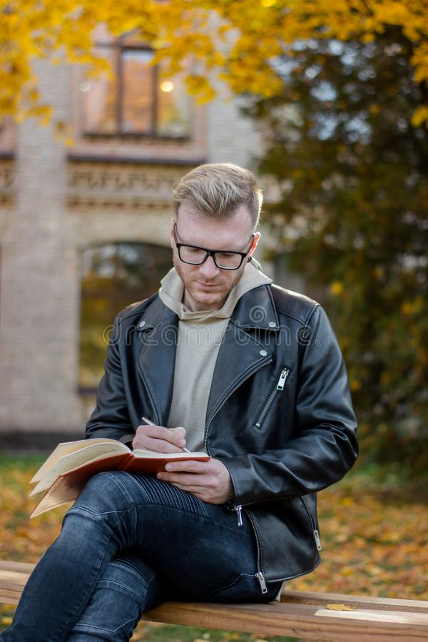 Smart guy writer in casual clothes makes notes in a notebook and sits on a park bench stock photo
