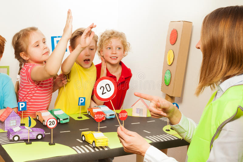 Smart happy kids studying traffic regulation rules stock photos