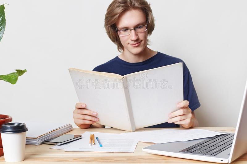 Smart hard working stylish male student wears spectacles, has attentive gaze in book, reads scientific literature before writing a stock photos