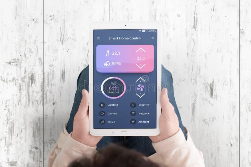 Smart hem- app för kontrollbegrepp på teblet i kvinnahänder arkivbild