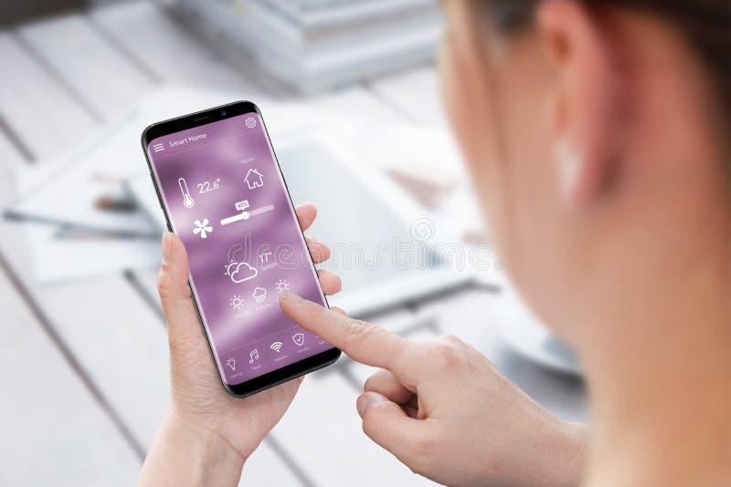 Smart hem- kontroll app för kvinnabruk på mobiltelefonen arkivfoto