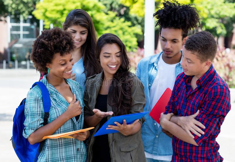 Smart hispanic female student learning with group of latin and african american young adults. Outdoor at campus of university stock photo