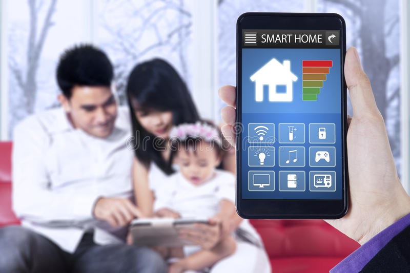 Smart home app and family in house. Close up of hand holding mobile phone with smart home applications on the screen and happy family sit on sofa at home stock photography