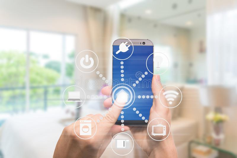 Smart home automation app on mobile with home interior in background. Internet of things concept at home. Smart technology 4.0 stock images