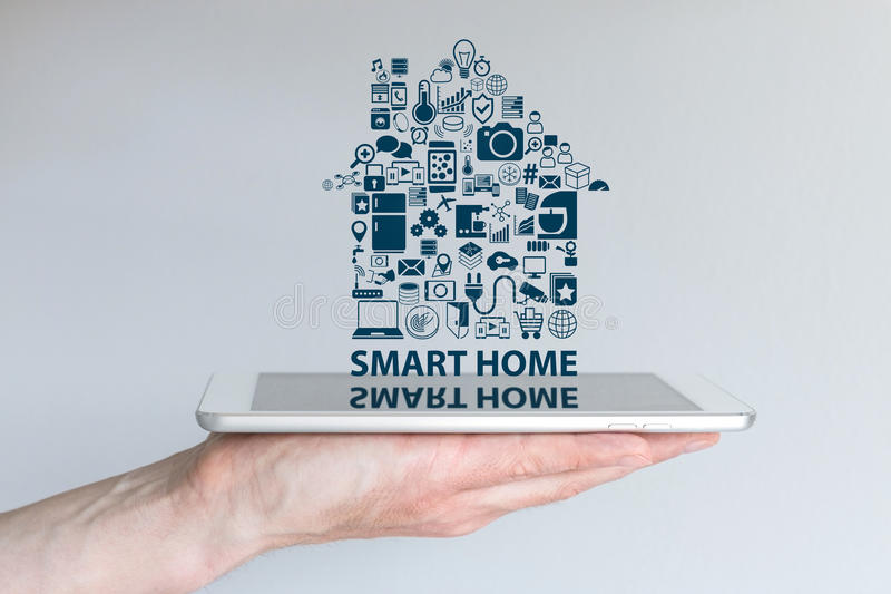 Smart home automation concept. Background with hand holding smart phone and floating text and icons. royalty free stock images