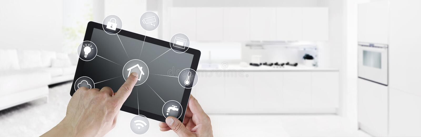 Smart home automation control hand touch digital tablet screen with white symbols on kitchen and living room background web. Smart home automation control hand stock image