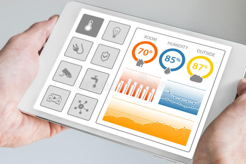 Smart home automation dashboard to control smart devices and sensors in the house or apartment. Hand holding modern tablet royalty free stock photo