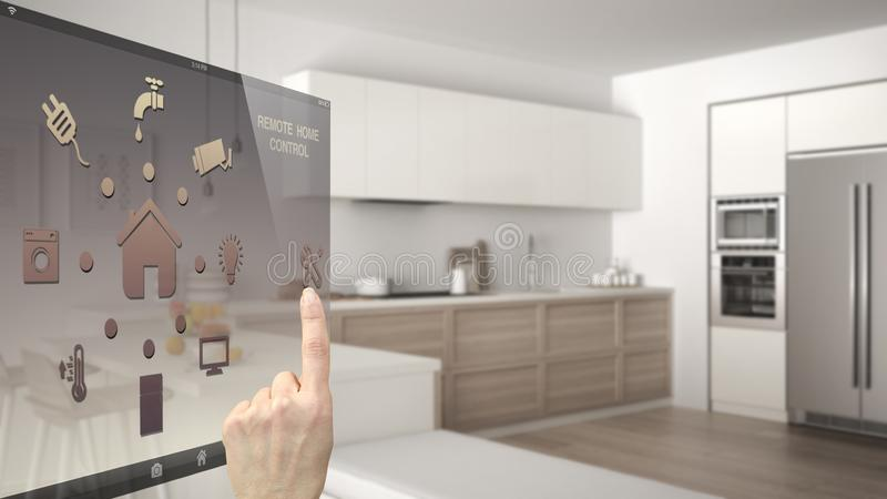 Smart home control concept, hand controlling digital interface from mobile app. Blurred background showing modern kitchen, archite stock photo