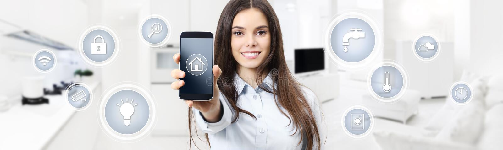 smart home control concept smiling woman showing cell phone screen with symbols on kitchen and living room blurred background stock photos