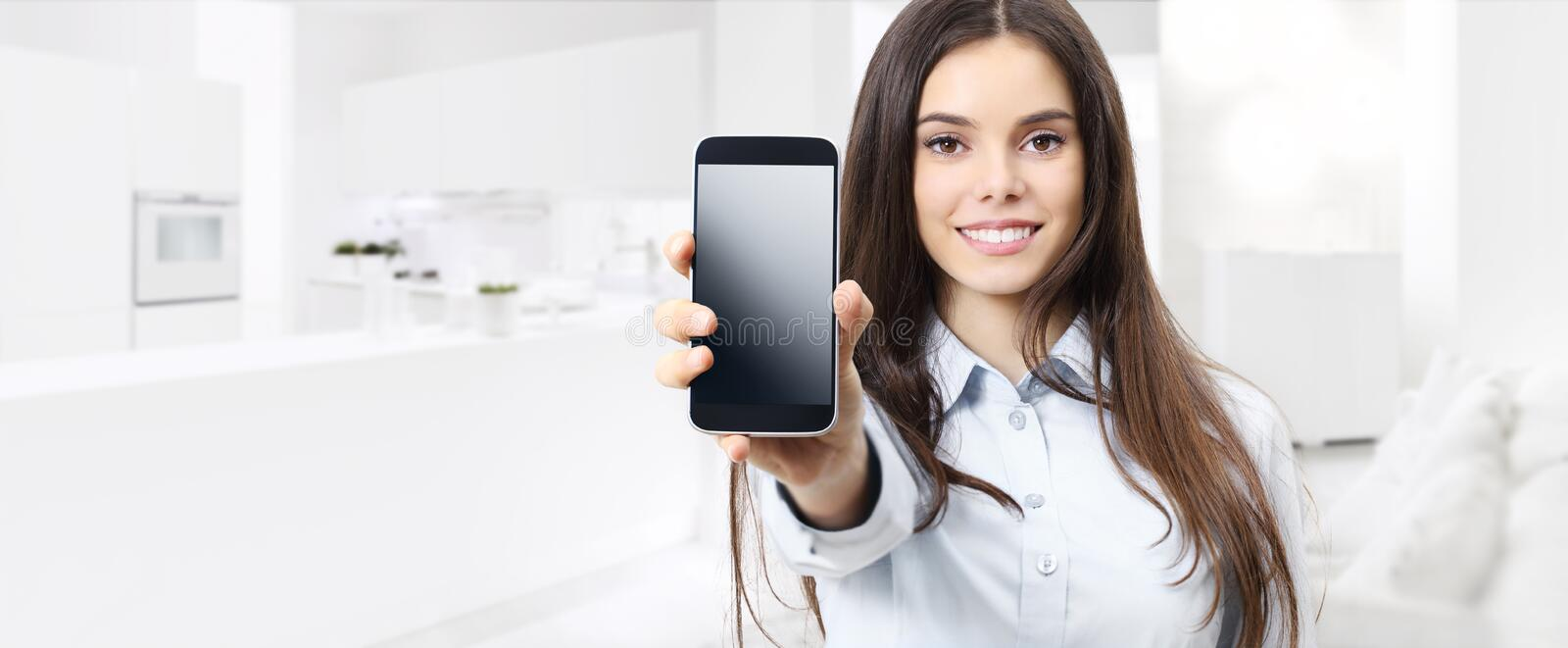 Smart home control concept smiling woman showing cell phone screen on kitchen and living blurred background royalty free stock photos