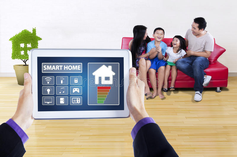 Smart home controller and happy family. Hands using a digital tablet as a remote control of smart home, shot with happy family on the background royalty free stock photos