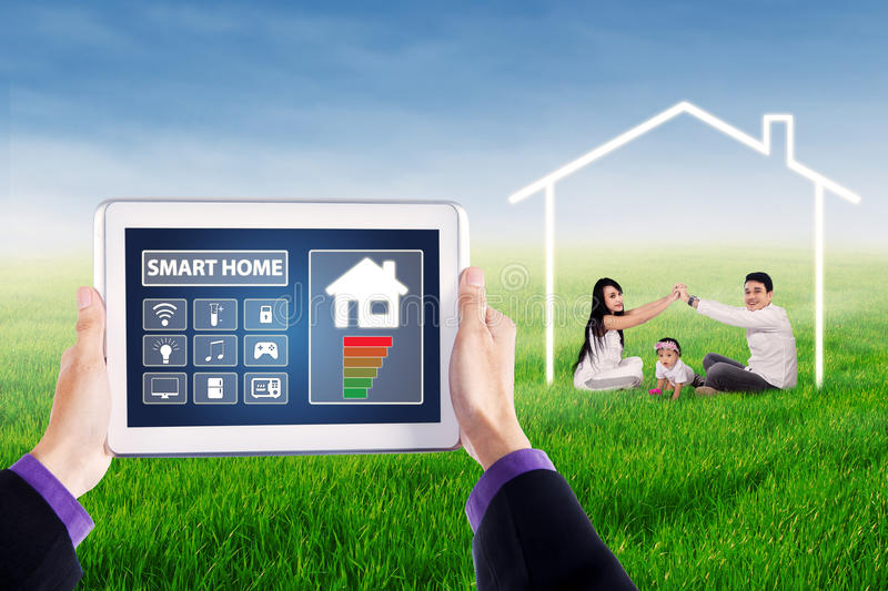 Smart home icons and happy family. Image of digital tablet with smart home controller icons and happy family playing on the park under a house symbol stock photo