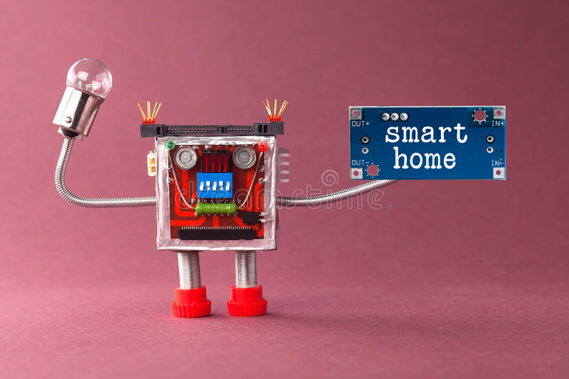 Smart home robotic automation concept. Colorful mechanical toy with light bulb lamp, blue circuit board and message royalty free stock photo
