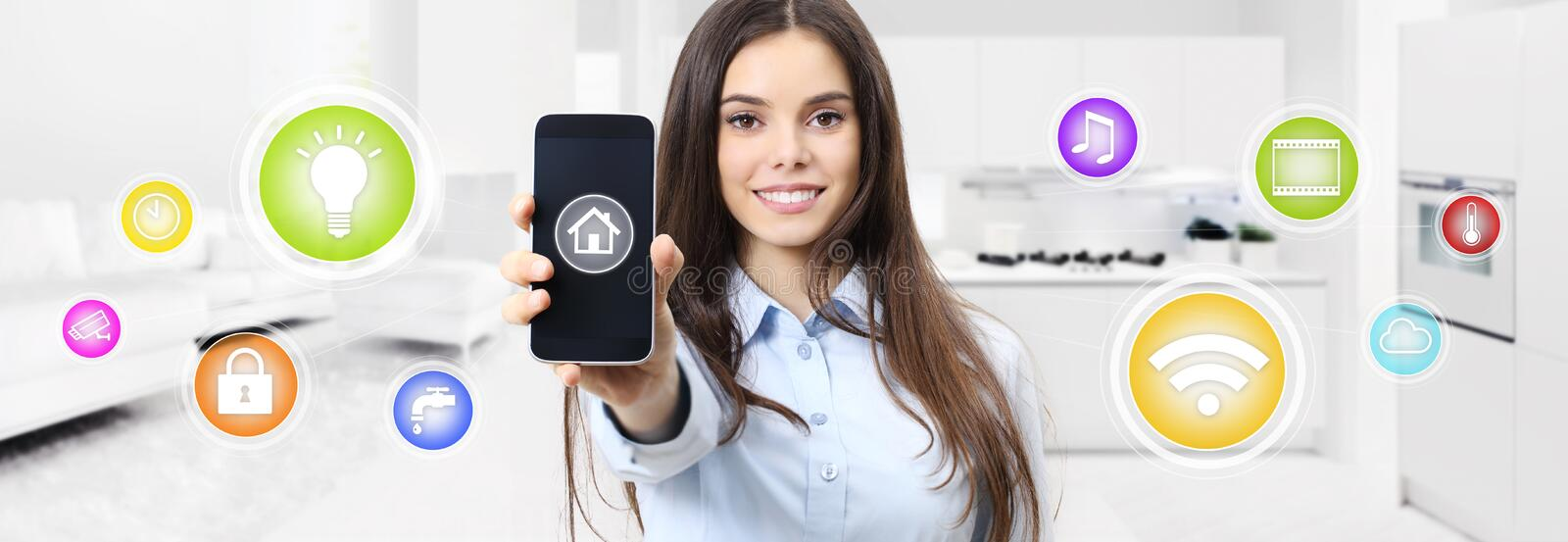 Smart home smiling woman showing cell phone screen with colored. Symbols on kitchen and living blurred background stock photography