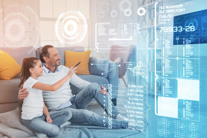 Happy girl using a smart house system while sitting with her father stock photos