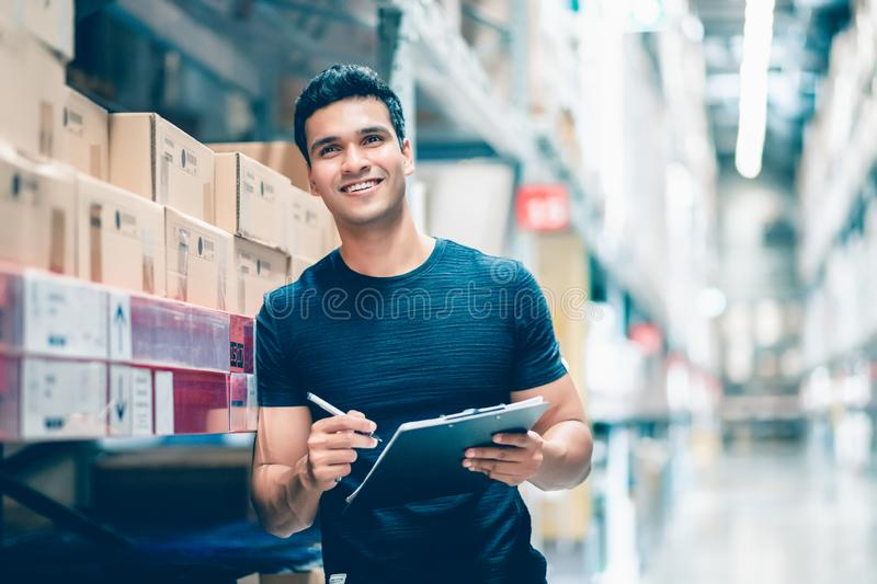 Smart Indian engineer man worker doing stocktaking of product management in cardboard box on shelves in warehouse. royalty free stock image