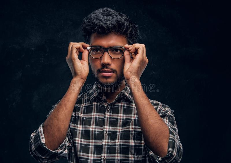 Smart Indian guy fixes his glasses and looking sideways. Smart Indian guy fixes his glasses and looking eways. Studio photo against a dark textured wall royalty free stock images
