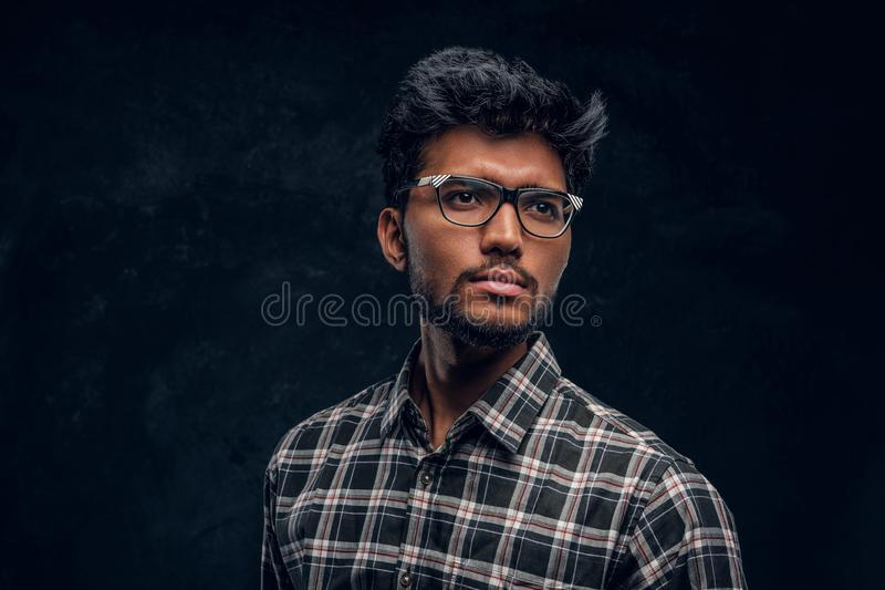 Smart Indian student wearing eyewear and a plaid shirt. Studio photo against a dark textured wall stock photos