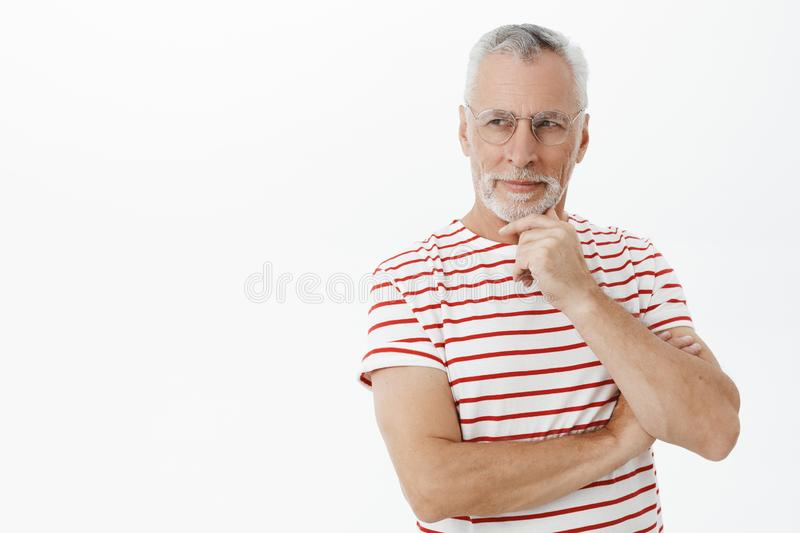 Smart, intelligent and creative senior father with grey hair rubbing beard thoughtfully smirking as if having stock photography