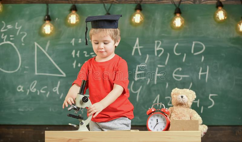 Smart kid concept. First former interested in studying, learning, education. Child on busy face near microscope. Kid boy stock photography