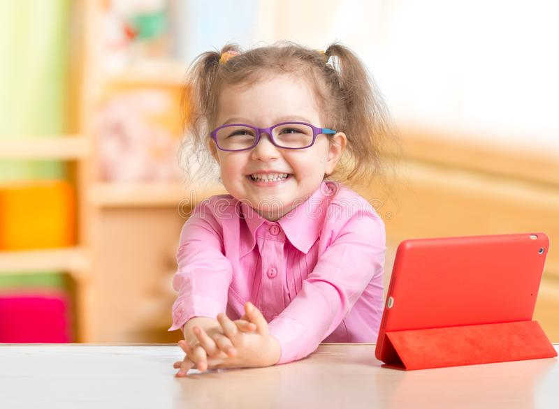 Smart kid in spectacles reading books in her room stock photo