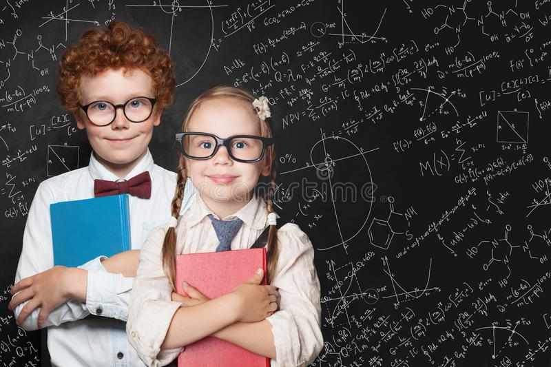 Smart kids portrait. Little girl and boy student holding books and standing against blackboard background with science and maths stock images