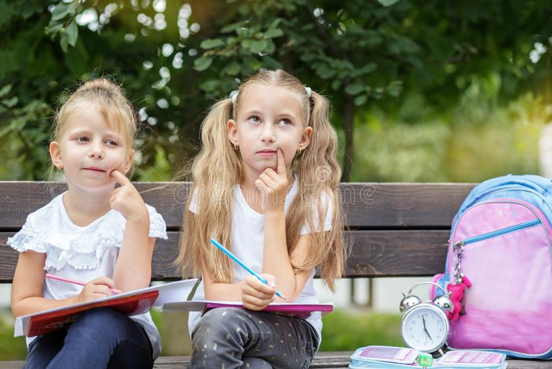 Smart kids think they are drawing in the schoolyard. The concept of school, study, education, friendship, childhood.  stock photography