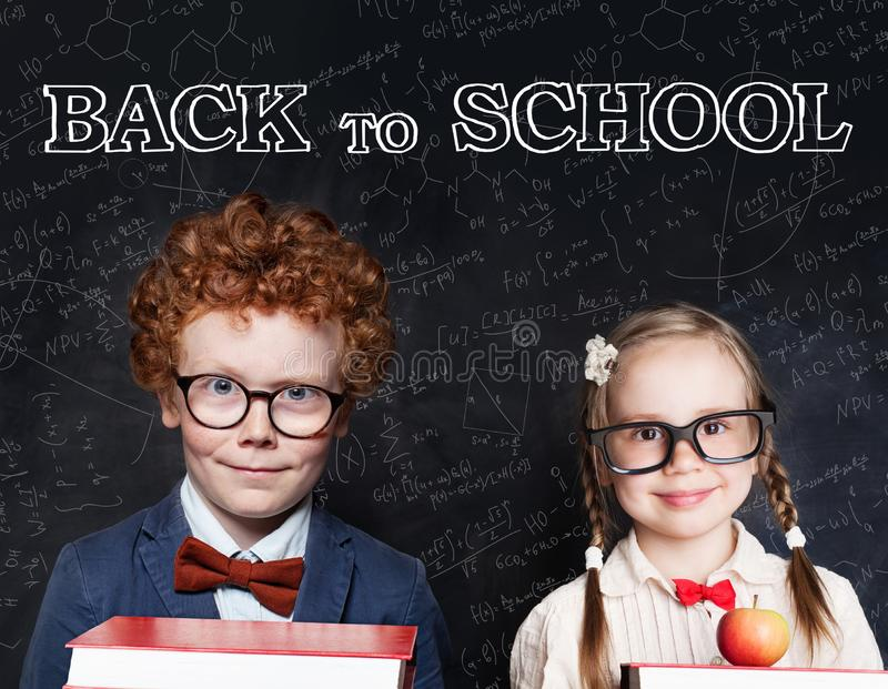 Smart kids wearing glasses holding books and smiling. Back to school concept royalty free stock photos