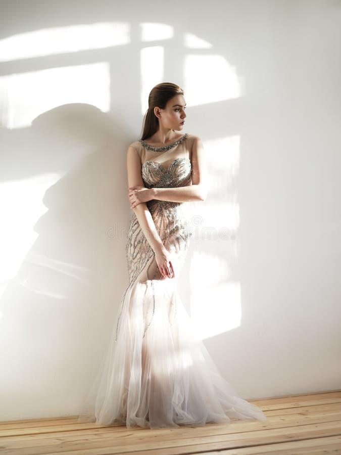 Smart klädde den fundersamma unga härliga kvinnan i det ljusa rummet i den eleganta beigea aftonklänningen som broderades av palj arkivfoton