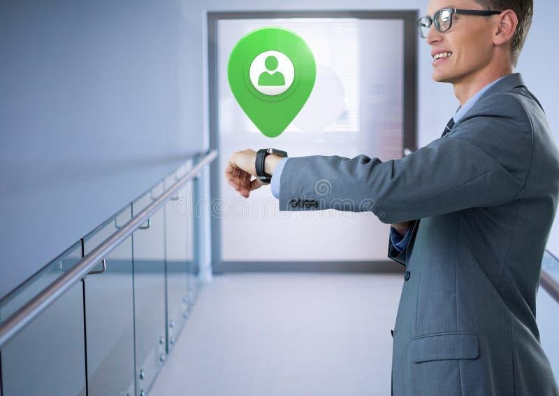 Smart klocka för affärsmaninnehav med app-lägemarkören i korridor royaltyfri fotografi