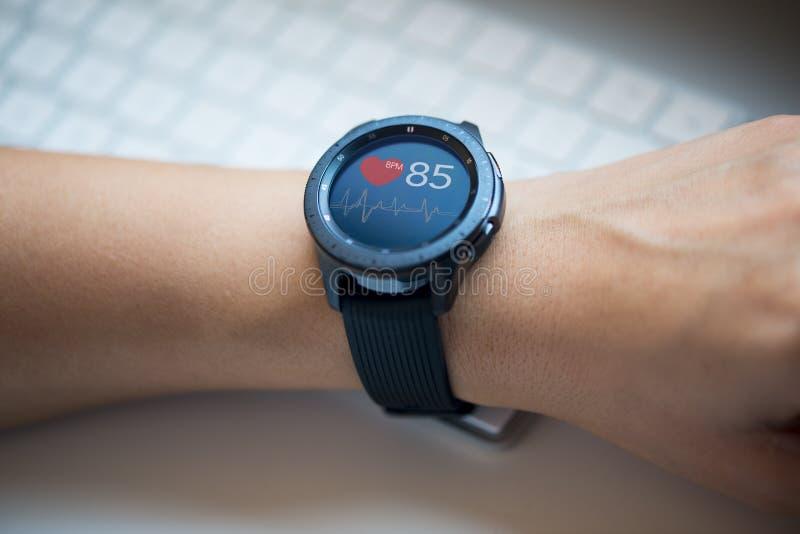 Smart klocka på woman'shanden som kontrollerar hjärtahastighet på kontoret arkivfoto