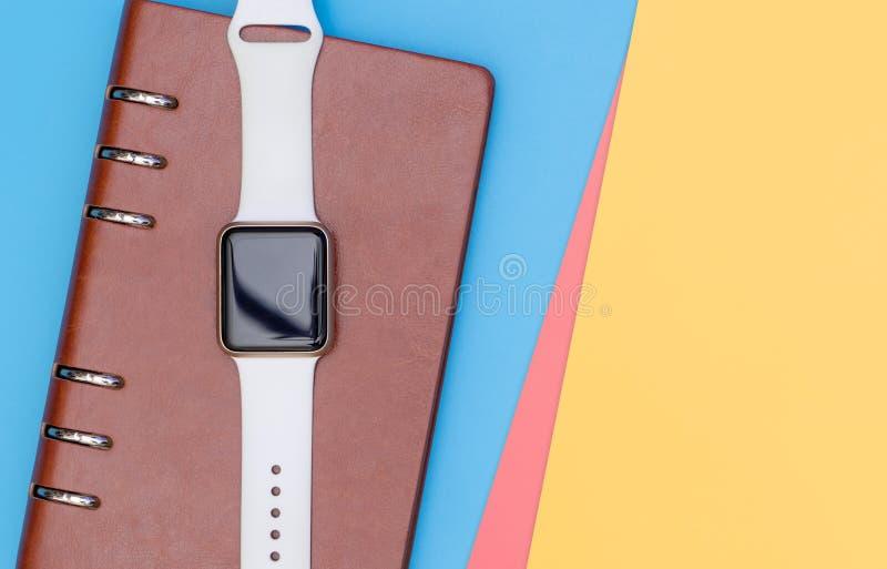 Smart klocka på anteckningsboken för att organisera med blå rosa skrän royaltyfri foto