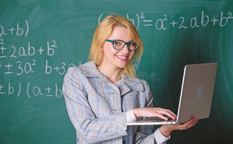 Smart klyftig dam f?r utbildare med den moderna b?rbara datorn som s?ker svart tavlabakgrund f?r information L?r det l?tta s?ttet royaltyfri foto