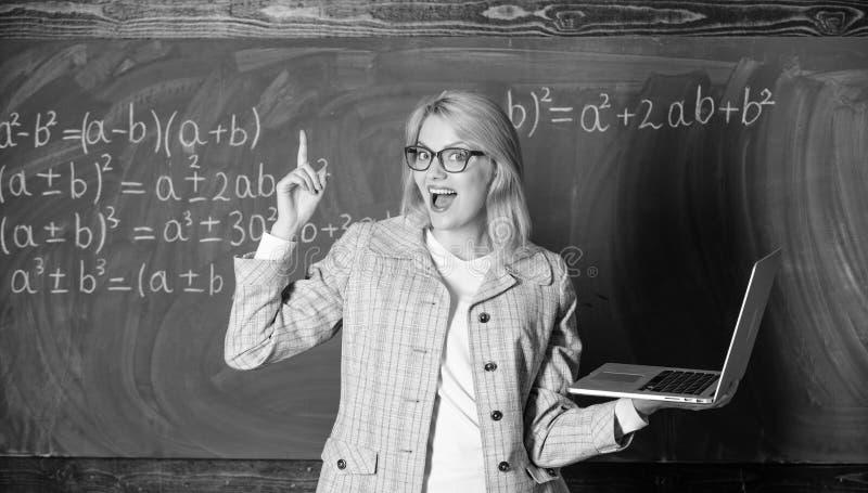 Smart klyftig dam f?r utbildare med den moderna b?rbara datorn som s?ker svart tavlabakgrund f?r information Online-skolg?ngbegre arkivfoto