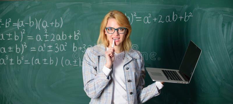 Smart klyftig dam f?r utbildare med den moderna b?rbara datorn som surfar svart tavlabakgrund f?r internet Begrepp f?r Digitala t royaltyfri fotografi