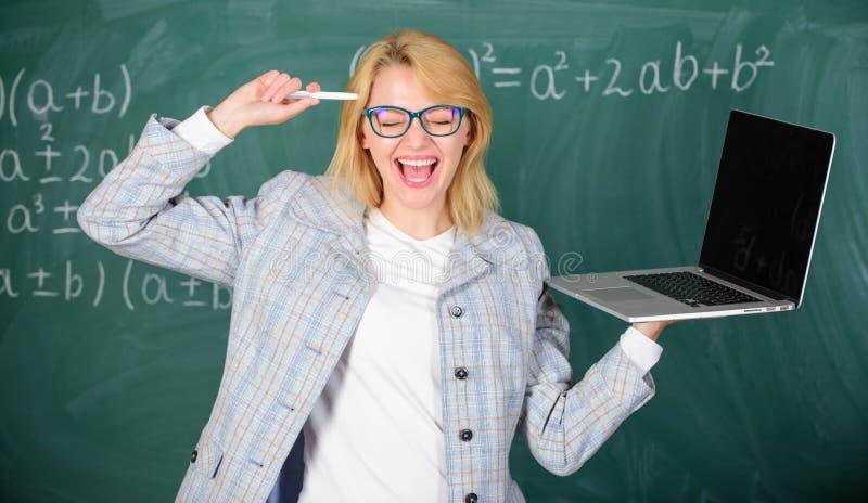 Smart klyftig dam f?r utbildare med den moderna b?rbara datorn som surfar svart tavlabakgrund f?r internet Id? p? hennes mening d fotografering för bildbyråer