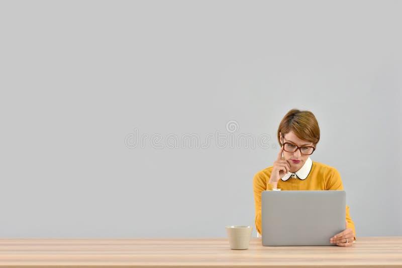 Smart kontorsarbetare bak den isolerade bärbara datorn royaltyfri fotografi