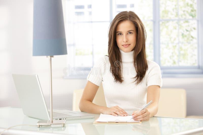 Smart kvinna som hemma arbetar arkivfoto
