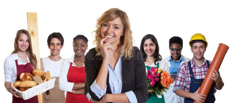 Smart kvinnlig affärsdeltagare i utbildning med gruppen av andra internationella lärlingar arkivfoto