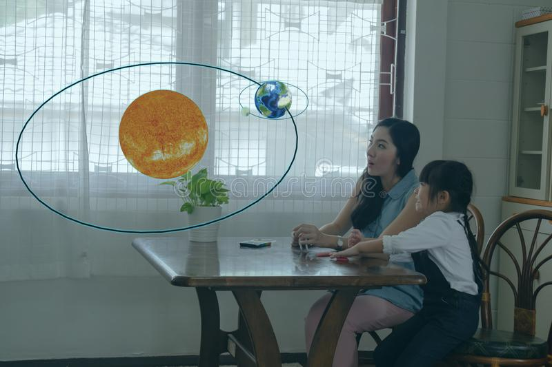Smart learning with augmented mixed virtual reality technology education concept, mother try to teach daughter by using artificial royalty free stock photos