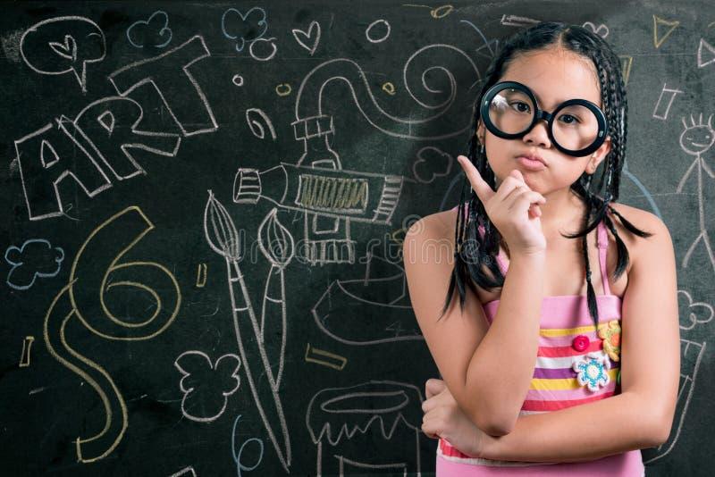 Smart liten flicka som framme ler av en svart tavla arkivfoton