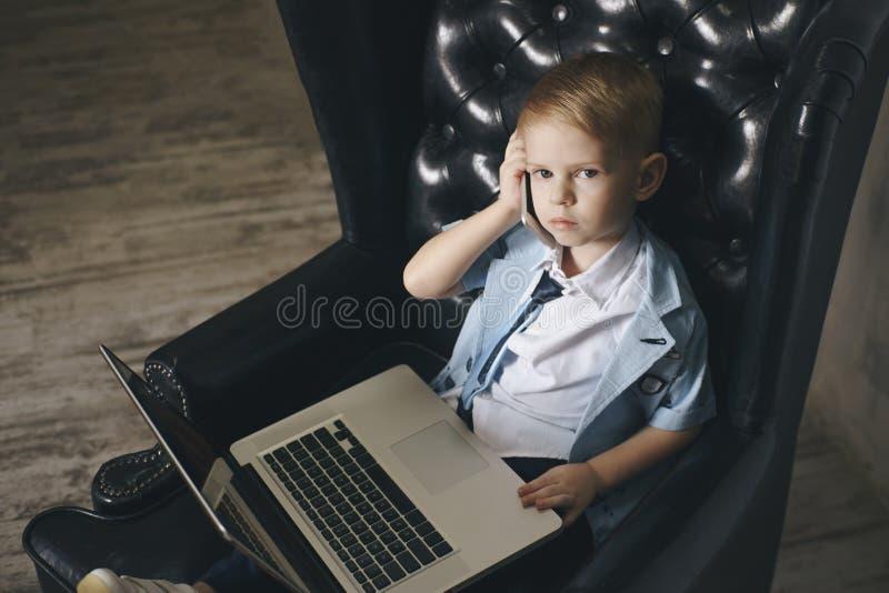Smart liten litet barnpojke med stora exponeringsglas som dricker kaffe, medan genom att använda hennes bärbar dator royaltyfri foto