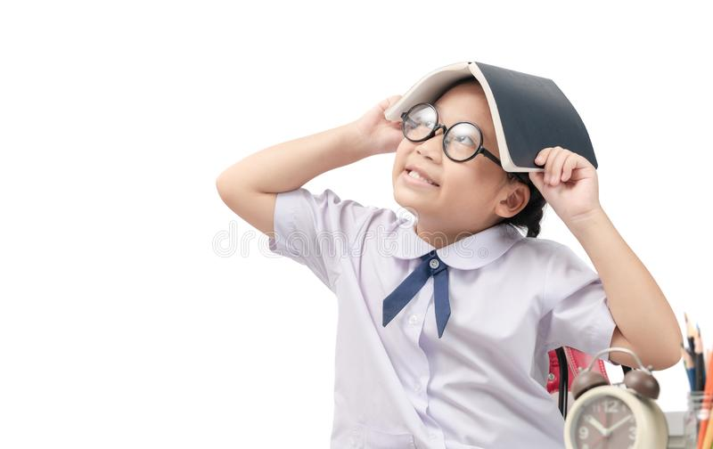 Smart little Asian girl thinking with book on head royalty free stock photo