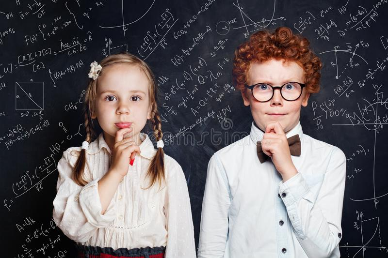 Smart little children thinking. Little boy and girl student on blackboard background with science and maths formulas royalty free stock photography