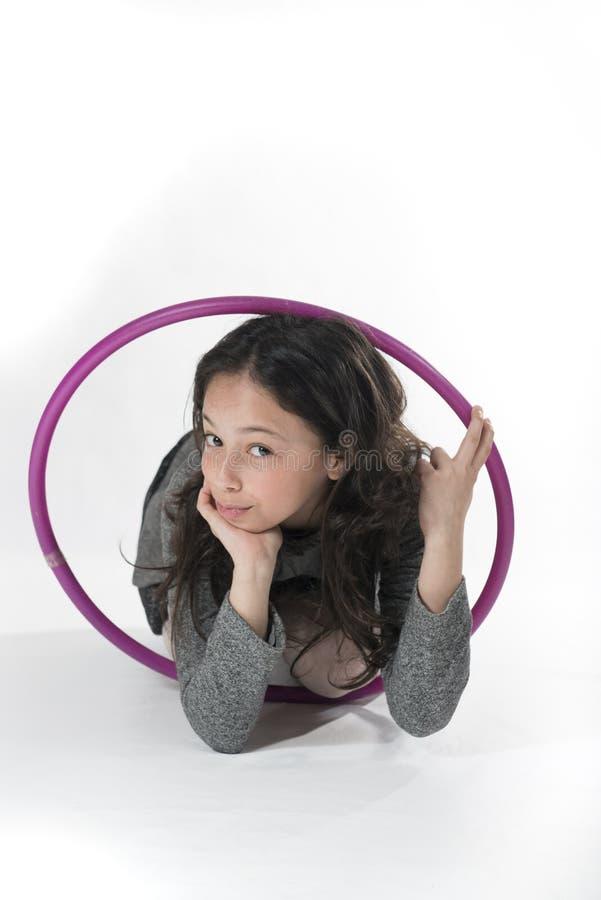 Smart Little Girl WIth Hoola Hoop. A smart little girl is posing with a purple hoola hoop. Grey background stock photos
