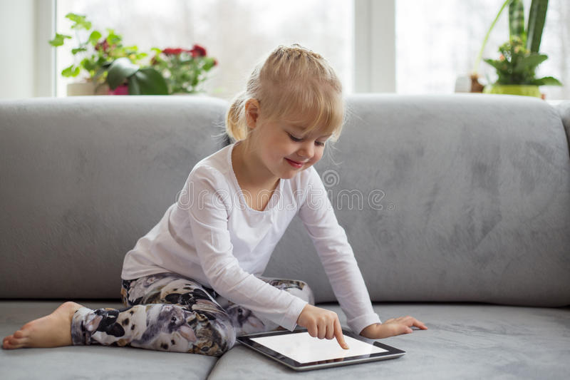 Smart little girl using tablet computer while sitting on couch in living room at home royalty free stock photos